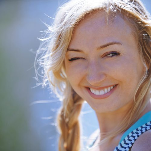 closeup image of young blonde woman smiling, eyes partially closed as she looks toward the sun. Her happiness represents the happiness one may feel after having taken a biological DNA TruAge test and being happy with the results.